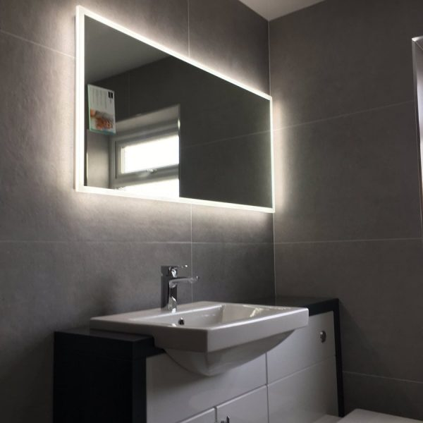 Bathroom with sink and lit mirror