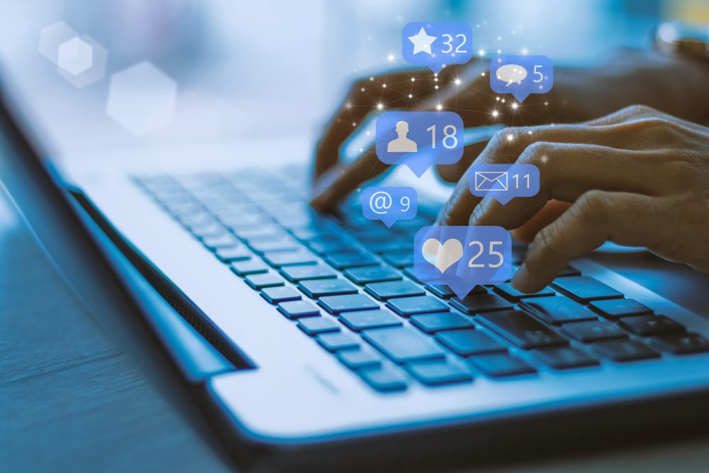 Typing on laptop with social media icons